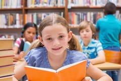 读在图书馆里的逗人喜爱的学生 免版税库存图片
