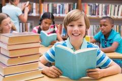 读在图书馆里的逗人喜爱的学生 免版税图库摄影