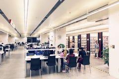 在图书馆里面,读和学习在图书馆里的人们 免版税库存图片