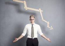 在图形前面的不满的生意人与负趋势。 免版税库存照片