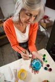 在图画班的资深妇女绘画碗 库存照片