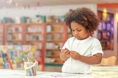 在图画的小的小孩女孩集中 混合非洲女孩学会和使用在幼儿园类 孩子享受手文字 免版税库存照片