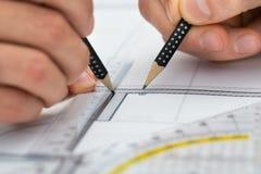 画在图纸的手特写镜头  免版税库存照片