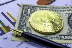 在图表背景的一金黄bitcoin 提供经费给电子技术帐户,统计,投资分析研究 免版税库存图片