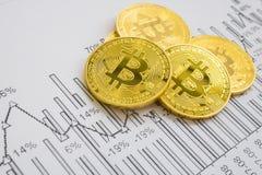 在图表背景的一金黄bitcoin 隐藏货币的贸易的概念 库存图片