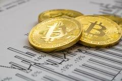 在图表背景的一金黄bitcoin 隐藏货币的贸易的概念 库存照片