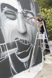 在图画和绘画期间的年轻街道画艺术家他的艺术品 免版税库存图片