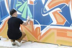 在图画和绘画期间的年轻街道画艺术家他的艺术品 库存照片