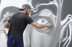 在图画和绘画期间的年轻街道画艺术家他的艺术品 库存图片
