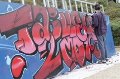 在图画和绘画期间的年轻街道画艺术家他的艺术品 图库摄影