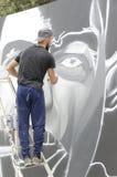 在图画和绘画期间的年轻街道画艺术家他的艺术品 免版税库存照片