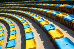 在圆形剧场剧院蓝色黄色塑料位子的透视对角曲线摘要视图 位子圈子 圆形剧场供以座位archi 免版税库存照片