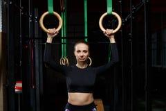在圆环的锻炼 在黑暗的健身房的锻炼 免版税库存照片