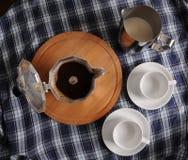 在圆的切板、一个投手牛奶和杯子的喷泉咖啡在蓝色格子花呢披肩桌布 免版税图库摄影