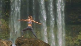 在圆的岩石的亭亭玉立的女孩姿势反对瀑布 股票视频