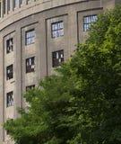 在圆的工厂厂房前面的绿色树 免版税库存照片