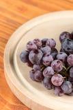 在圆的木厨房的特写镜头宏观葡萄在桌上上 库存照片