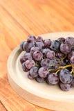 在圆的木厨房的特写镜头宏观葡萄在桌上上 免版税库存照片