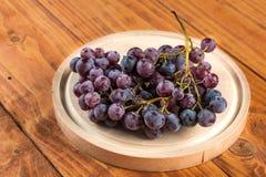 在圆的木厨房的葡萄在桌上上 库存照片