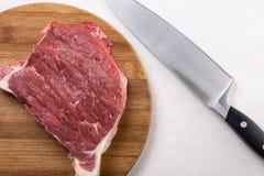 在圆的木板的未加工的牛排有厨房在白色大理石的厨师刀子的 免版税库存图片