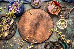 在圆的木板附近的健康药草浸剂设置在土气背景,顶视图 库存照片