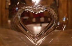 在圆的玻璃花瓶特写镜头的玻璃心形的孔 库存图片