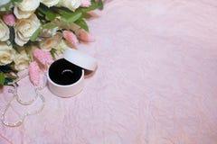 在圆的白色箱子的定婚戒指在桃红色纸背景和有白玫瑰和lagurus花束的  顶层 免版税图库摄影