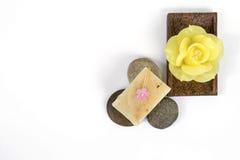 在圆的石头和黄色玫瑰蜡烛的自然肥皂酒吧 免版税库存照片