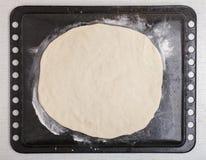 在圆的薄饼形状的发酵面团在烘烤盘子 免版税库存图片
