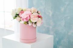 在圆的豪华当前箱子的花 桃红色和白色牡丹花束在纸箱的在窗口附近 帽子箱子大模型  免版税库存照片