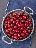 在圆的金属碗的水多的樱桃 库存照片