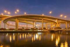 在圆的高速公路交叉点河前面和反射的蓝色暮色天空 图库摄影