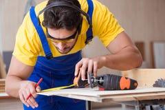 在圆锯的年轻安装工木匠运作的切口木头 图库摄影