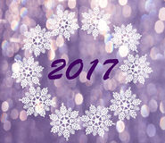 在圈子的雪花在与数字的紫色bokeh背景 免版税库存图片
