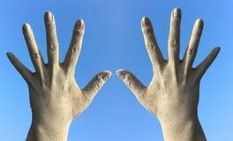 在土和尘土的两只女性手从被展开的手指a 免版税库存照片
