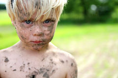 在土和泥盖的严肃的小男孩外面 库存图片