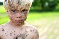 在土和泥盖的严肃的小男孩外面 库存照片