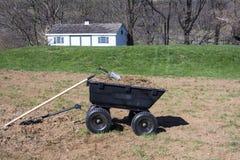 在土和草的园艺工具在围场推车 库存照片