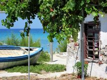 在土地的老渔夫小船在被放弃的房子旁边在希腊,哈尔基季基州 库存图片