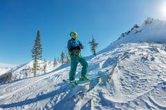 在土坎顶部供以人员滑雪者讨便宜者的身分,冒险冬天freeride极端体育 库存照片