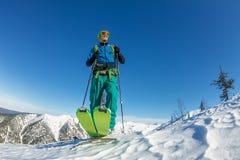 在土坎顶部供以人员滑雪者讨便宜者的身分,冒险冬天freeride极端体育 免版税库存图片