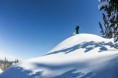在土坎顶部供以人员滑雪者讨便宜者的身分,冒险冬天freeride极端体育 库存图片