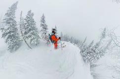 在土坎顶部供以人员滑雪者讨便宜者的身分,冒险冬天freeride极端体育 免版税库存照片