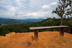 在土壤峭壁现象的位子天生在森林山小山与多云天空的 免版税库存照片