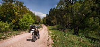 在土森林公路,enduro,活跃生活方式,旅行恋人概念的冒险摩托车 免版税库存照片