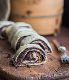 在土气书桌上的切的罂粟种子果馅奶酪卷有在蛋糕旁边的叉子的 库存照片