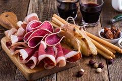 在土气党桌上的熏制的肉开胃小菜盛肉盘 库存照片