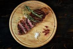 在土气切板的切的半生半熟烤牛排用迷迭香和香料,黑暗的土气金属背景,上面 库存照片