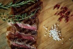 在土气切板的切的半生半熟烤牛排用迷迭香和香料,黑暗的土气金属背景,上面 免版税库存图片