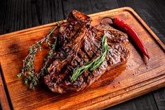 在土气切板的半生半熟烤牛排用迷迭香和香料,黑暗的土气木背景,顶视图 库存照片